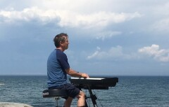 picture of Pierre playing the piano in front of the St. Lawrence river
